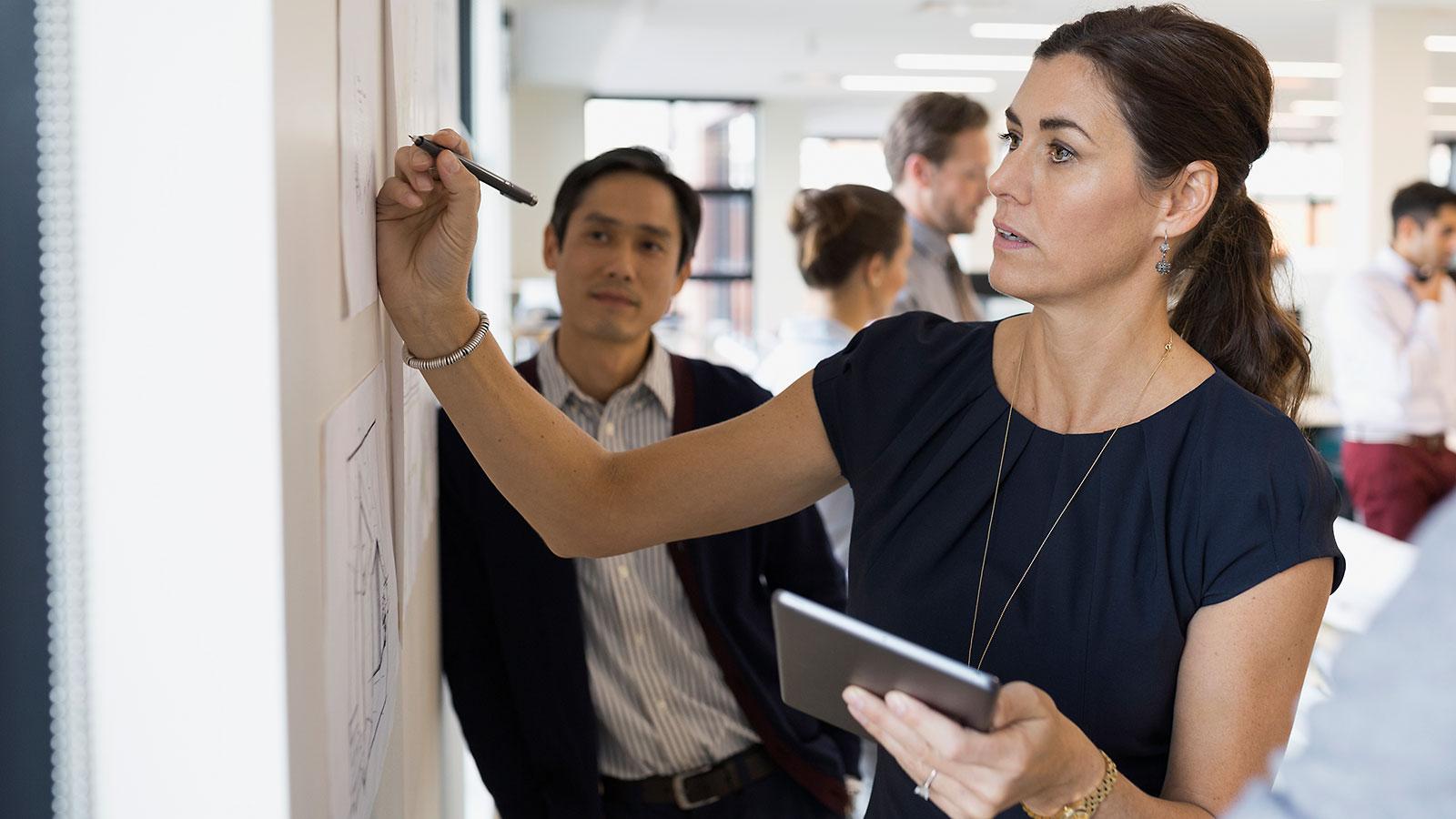 Forretningskvinne skriver på whiteboard og holder nettbrett i den ene hånden mens mannlig kollega følger med.