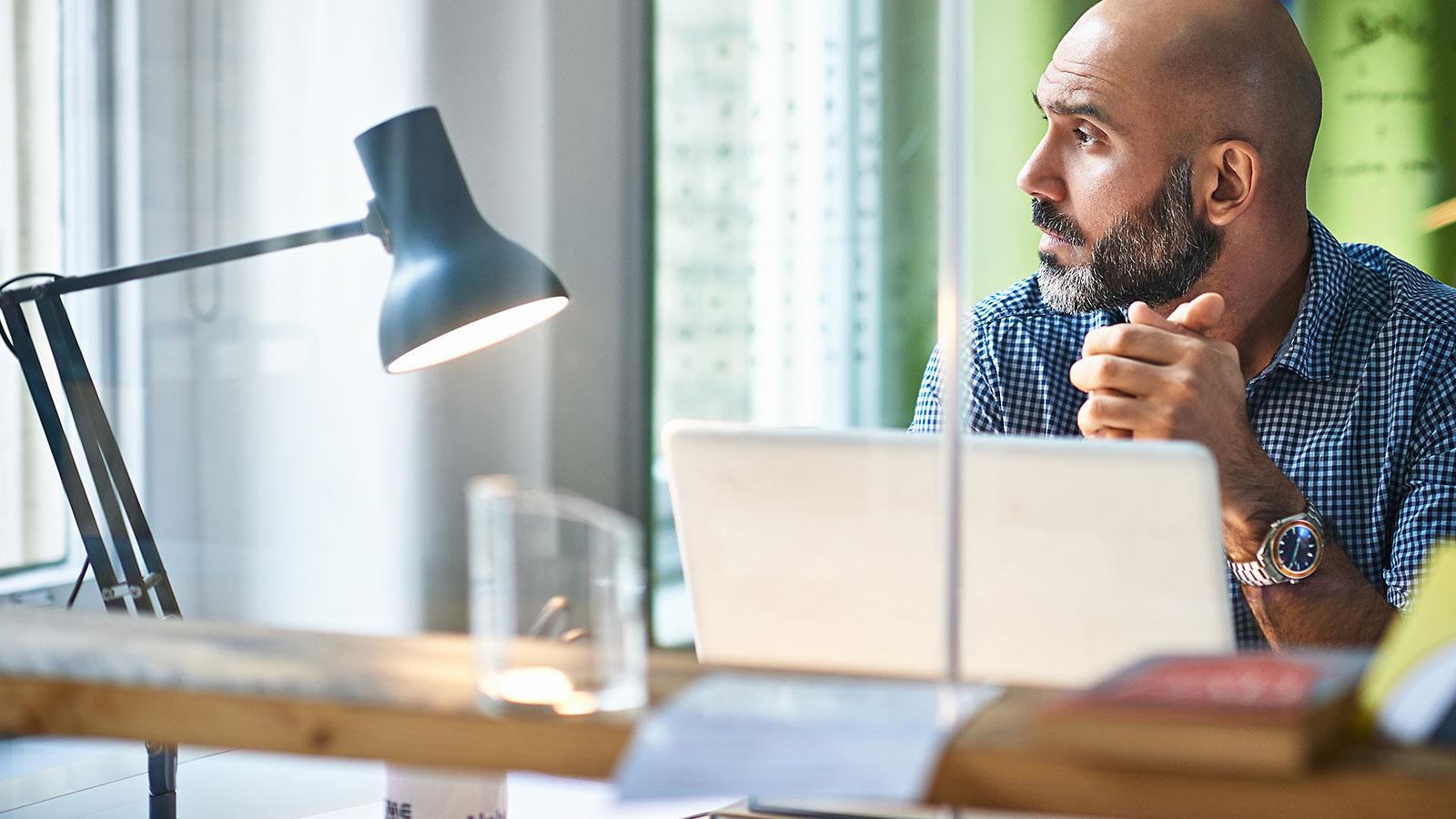 Mann jobber ved laptop og ser ut av vinduet
