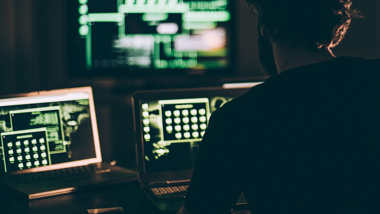 Mann jobber med cybersikkerhet i mørket på noen datamaskiner